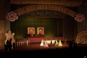 Women carry a flag of the April Spring People's Art Festival to raise it on the stage at the East Pyongyang Grand Theater in Pyongyang, North Korea, Thursday, April 11, 2013. The festival opened Thursday to mark late president Kim Il Sung's birthday on April 15, known in North Korea as the Day of the Sun. Portraits in the background show Kim Il Sung, left, and his son Kim Jong Il. (AP Photo/Jon Chol Jin)